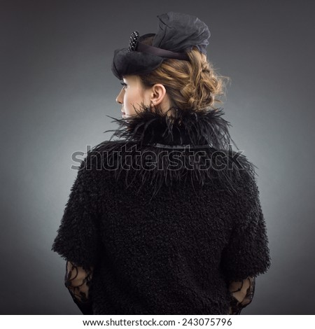 Fashion Image. Portrait of a young woman in a stylish retro black dress. - stock photo