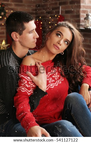 fashion interior holiday Christmas photo of beautiful tender couple, in cozy clothes celebrating New Year holidays