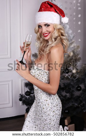 fashion interior photo of beautiful girl with blond hair posing beside Christmas tree in Santa hat