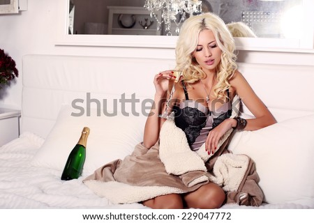 fashion interior photo of beautiful sensual woman with blond hair in lingerie corset lying on bed with glass of champagne - stock photo