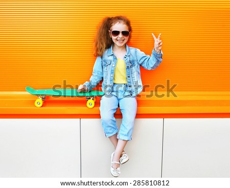 Fashion kid. Stylish little girl child wearing a summer or autumn jeans clothes, sunglasses with skateboard having fun in city over colorful orange background