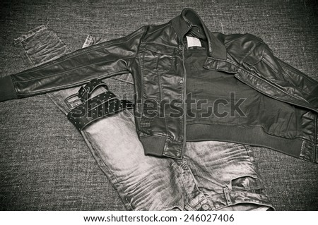 Fashion: Leather jacket, jeans with a leather belt. Retro style, black-and-white photo - stock photo