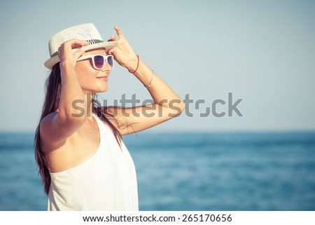 Fashion Lifestyle, Beautiful girl in the sunglasses and white hat on the beach at the day time. Travel and Vacation. - stock photo