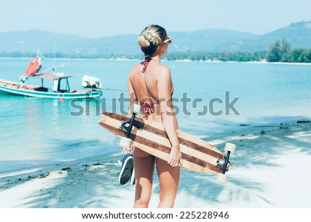 Fashion lifestyle outdoors. Sporty woman with longboard in hand walking on white sand on tropical beach - stock photo