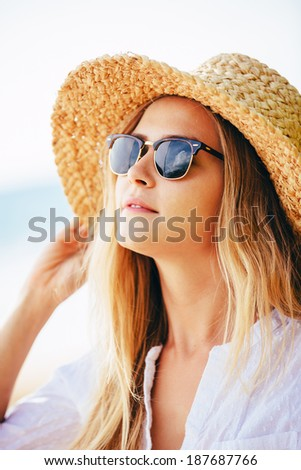 Fashion lifestyle, Portrait of beautiful blond girl on the beach in sunhat and sunglasses. - stock photo