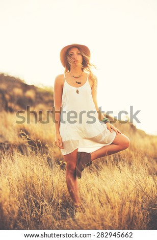 Fashion Lifestyle, Portrait of Beautiful Young Woman Backlit at Sunset Outdoors. Soft warm color tone. - stock photo