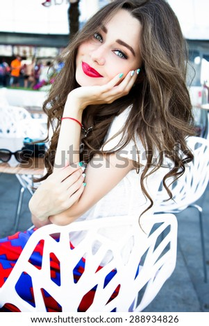 Fashion lifestyle portrait of pretty young hipster seductive woman with bright sexy make up,wearing stylish t shirt and skirt,White urban wall background.Sit at street cafe and waiting for her order - stock photo