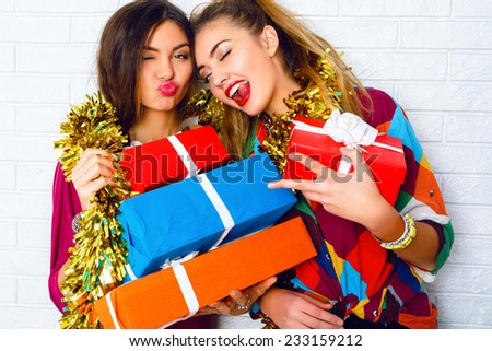 Fashion lifestyle portrait of two girls friends holding birthday bright presents, wearing trendy clothes and sparkled tinsel. Going crazy, and making funny faces. - stock photo