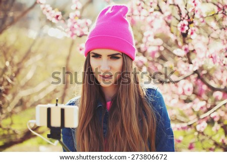 Fashion lifestyle portrait of young lovely woman wearing a trendy cap, a bright youth clothing, and making selfie with a stick against pink spring flowers. Having fun, joy and happiness. - stock photo