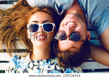 Fashion lifestyle portrait of young perfect couple lay and relaxed on their vacation, wearing sunglasses and vintage clothes, bright sunny summer colors. - stock photo