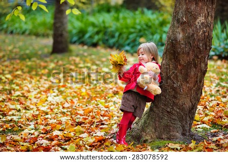 Fashion little girl at autumn background play with toy - stock photo