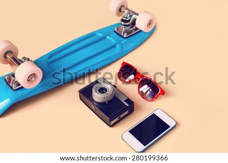 Fashion look concept. Blue skateboard, red sunglasses, vintage camera and screen smartphone. Trendy colorful photo - stock photo