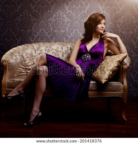 Fashion luxury model in purple dress. Young beauty style girl. Beautiful luxurious woman sitting on a gold vintage couch  - stock photo