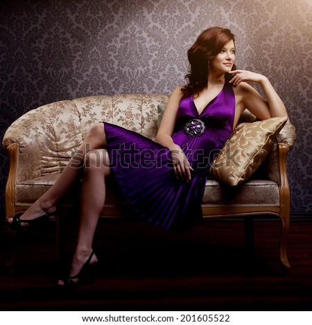 Fashion luxury model in purple dress. Young beauty style girl. Beautiful luxurious woman sitting on a gold vintage couch
