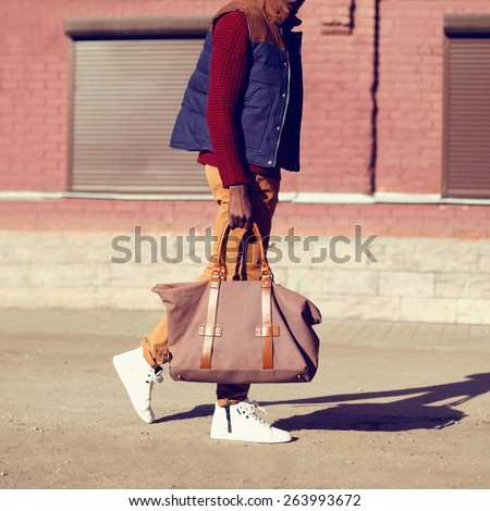 Fashion male look. Trendy stylish handsome man walking outdoors in the city - stock photo