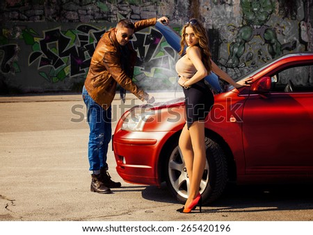 Fashion male model repairng car for voluptuous blonde young woman outdoors - stock photo