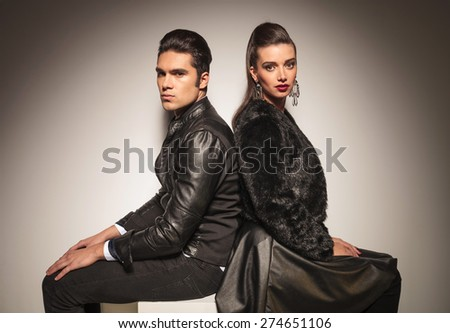 Fashion man and woman sitting back to back while holding their hands on the legs. - stock photo