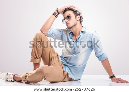 Fashion man holding his hat with his rigth hand while sitting on the floor, looking away. - stock photo