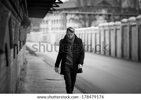 fashion man is walking close to the road in black coat  - stock photo