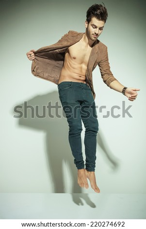 Fashion man jumping against grey background, pulling his jacket while looking down - stock photo