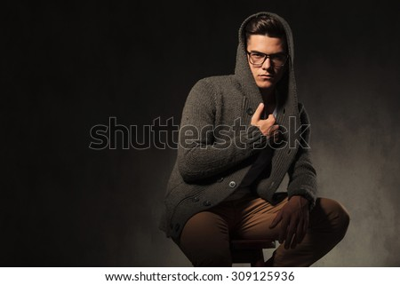 Fashion man sitting while pulling his sweater, on grey studio background.