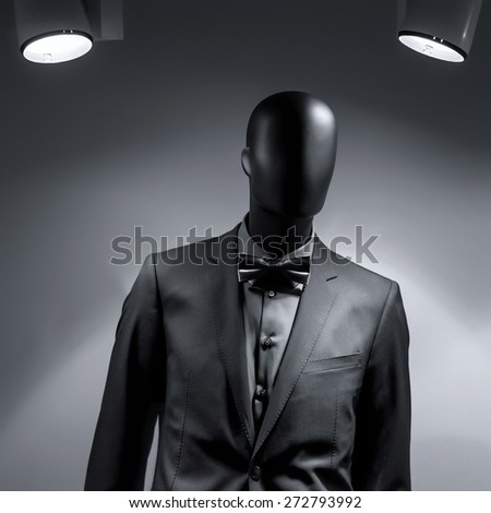 Fashion mannequin in elegant black suit over dark grey background under lights of two lamps. Black White Photo - stock photo