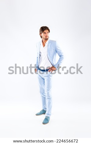 Fashion men, male model wear blue suit, young man profile full length portrait looking side copy space over gray background