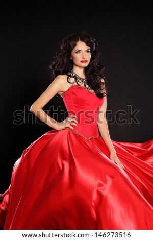 Fashion model. Beautiful woman wearing in magnificent red dress isolated on black background.  - stock photo