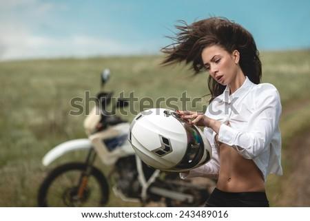 Fashion model Biker girl next to motorcycle  - stock photo