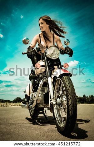 Fashion model biker girl on a motorcycle - stock photo