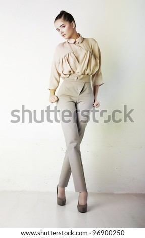 Fashion model female in light trousers and shirt standing in studio - stock photo