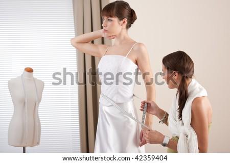 Fashion model fitting white wedding dress in professional fashion designer studio - stock photo
