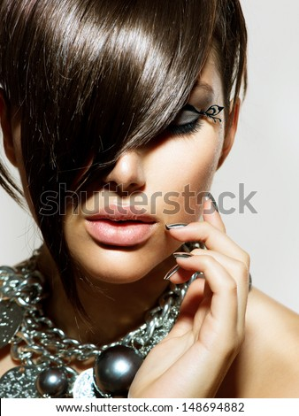 Fashion Model Girl Portrait. Trendy Hair Style. Short Haircut. Hairstyle. Beauty Woman closeup. Fringe. Hairdressing. Silver Metallic Accessories and Manicure - stock photo