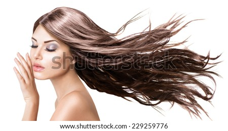Fashion Model Girl Portrait with Long Blowing Hair. Glamour Beautiful Woman with Healthy and Beauty Brown Hair isolated on white background touching her face. Skin care and beautiful hair concept