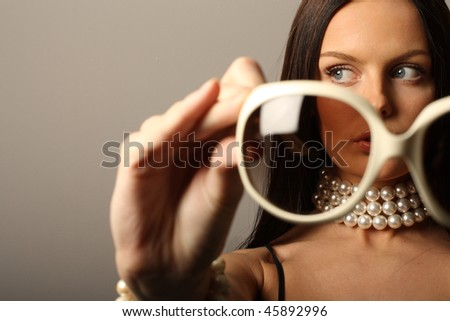 Fashion model holding big white sunglasses and pearls necklace. - stock photo