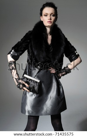 fashion model holding little purse in light background posing - stock photo