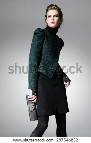 fashion model holding purse in light background - stock photo
