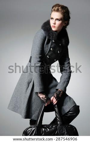 fashion model in coat clothes holding handbag posing-gray background - stock photo