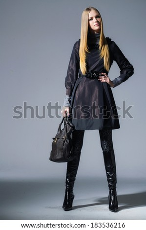 fashion model in fashion dress with bag  posing on gray background - stock photo