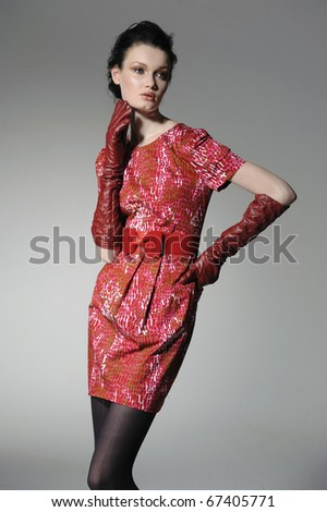 fashion model in fashion red dress posing in light background