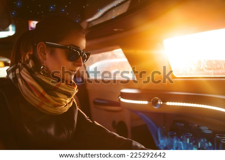 Fashion model in leather jacket and sunglasses sitting in limousine in sunlights - stock photo