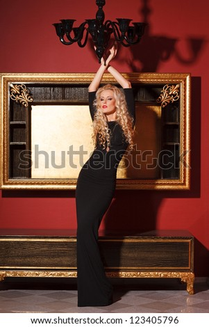 Fashion model in long black dress posing in glamorous interior - stock photo