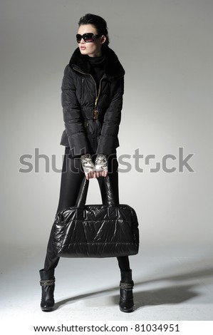 fashion model in modern clothes wearing sunglasses holding handbag posing on gray background