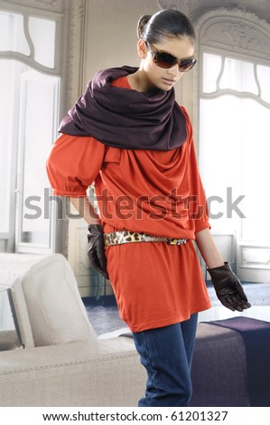 fashion model in modern red dress wearing sunglasses posing in the studio - stock photo