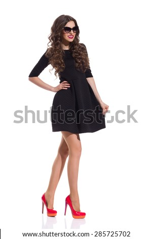 Fashion Model in Red High Heels And Black Mini Dress. Full length studio shot isolated on white. - stock photo
