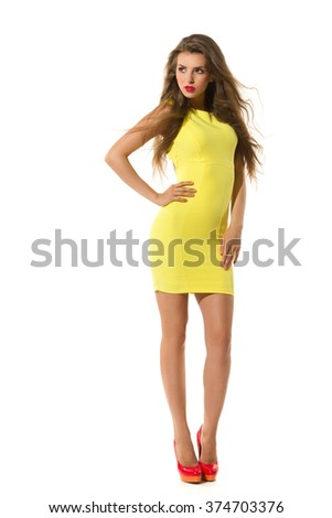 Fashion model in slim yellow mini dress and red high heels posing with hand on hip and looking away. Full length studio shot isolated on white. - stock photo
