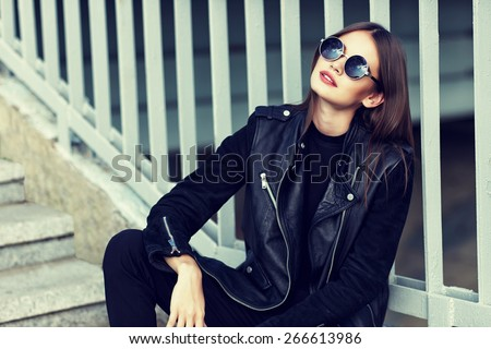 fashion model in sunglasses and black leather jacket posing outdoor - stock photo