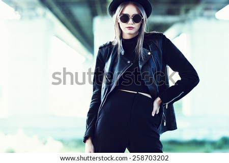 fashion model in sunglasses, hat and black leather jacket posing outdoor.  - stock photo