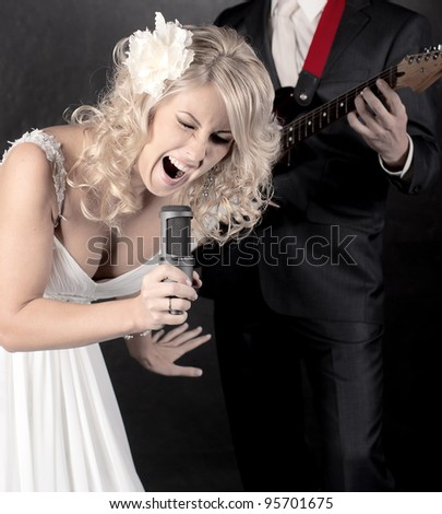 Fashion model in wedding dress with microphone in hand - stock photo