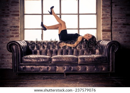 Fashion model lying on leather couch - Beautiful mixed race woman posing - Concepts about beauty,fashion and lifestyle - stock photo